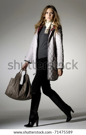 High fashion model with bag posing in the studio - stock photo