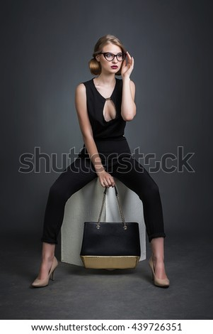 High fashion model with glasses and bag posing