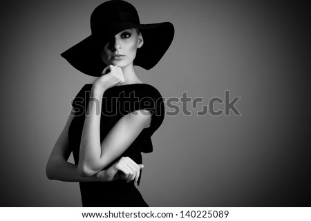 high fashion portrait of elegant woman in black and white hat and dress. Studio shot - stock photo