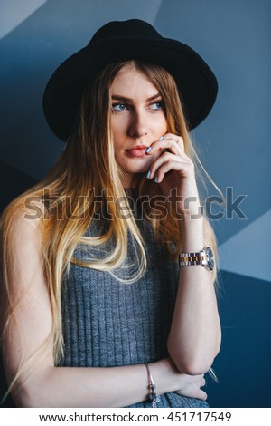 high fashion portrait of elegant woman in black  hat and dress. Studio shot