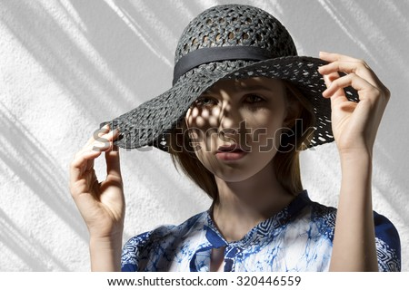 high fashion portrait of elegant woman with hat and shirt. Looking in camera with her beautiful face in half-light  - stock photo