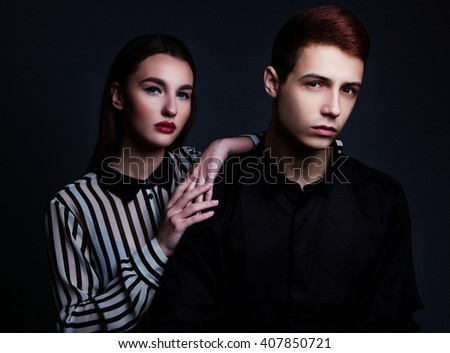 High fashion portrait of young elegant couple over black background. - stock photo