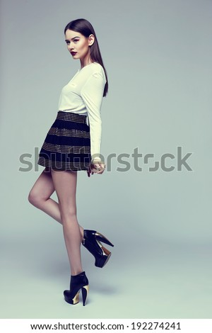 high fashion portrait of young elegant woman in black skirt and white blouse. Studio shot  - stock photo