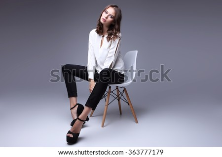 high fashion portrait of young elegant woman. White blouse, black pants, shoes. Studio shot  - stock photo