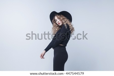 High fashion shot of elegant woman in a hat and long dress. - stock photo