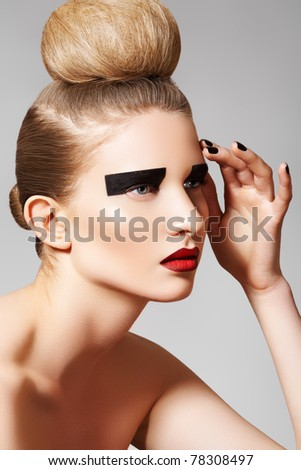 High fashion style. Cosmetics and make-up. Beautiful woman model with perfect clean skin, creative black eye make-up, dark red lips and fashion bun hairstyle. Blond chignon bun on her head - stock photo