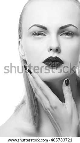 High fashion vogue style, manicure, cosmetics and make-up. Studio portrait of female caucasian young blonde model with black lipstick and nails isolated on white background. Black and white