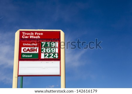 High gas prices sign with blue sky background - stock photo