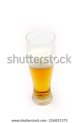 High glass with light beer stands on the table