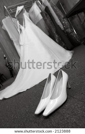 High heel wedding pumps with wedding dress hanging up in the background.  Photo is in black and white. - stock photo
