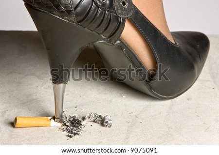 High-heeled stiletto shoe crushing a cigarette on the floor