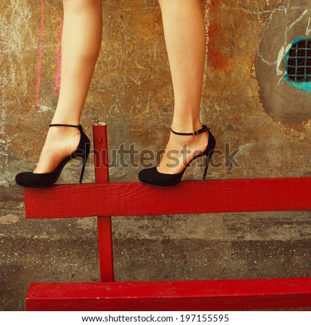 High heels concept. Sexy legs with trendy black chamois shoes over vintage background. Suprematism style. Outdoor fashion shot