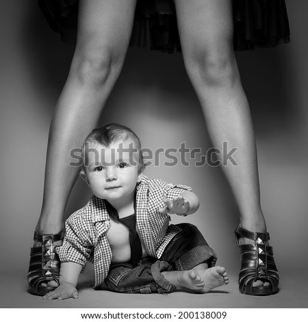 High heels family concept. Stylish baby boy standing with his fashionable mother. Girl in stylish peep toes shoes. Hipster style boy. Black and white (monochrome) studio shot