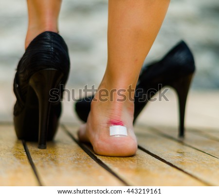 High heels hurts very often, feet with white little patch on ankle, one feet on the floor and other with black shoe
