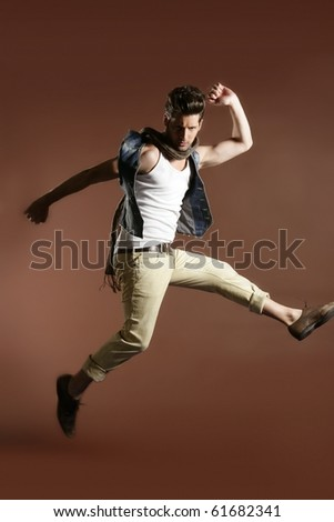 High jumping fly young handsome fashion man on brown background - stock photo