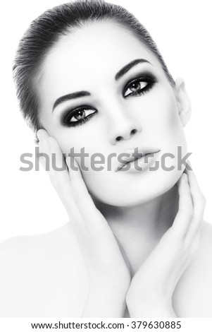 High key black and white portrait of young beautiful healthy woman with smoky eyes make-up touching her face - stock photo