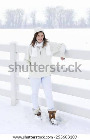 High key image of a pretty teen brunette bundled in white in a snowy white setting. - stock photo