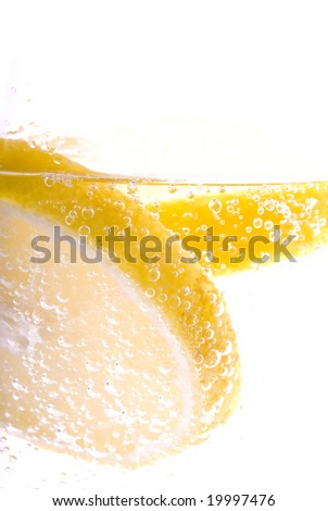 High Key macro image of lemon slices floating in bubbly mineral water. - stock photo