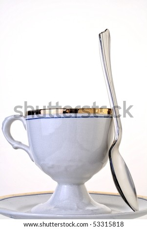 High-key photo of an antique cup,saucer and spoon on white background.