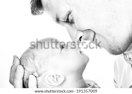 High key portrait in black and white, of a father lovingly embracing his newborn son - stock photo
