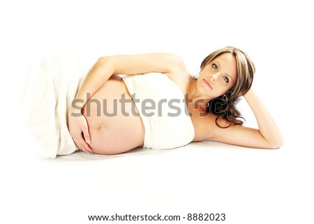 High-key portrait of a pregnant woman with serious expression - stock photo