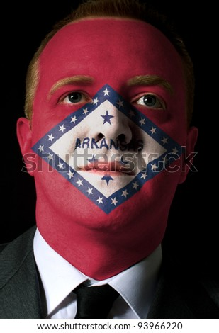 High key portrait of a serious businessman or politician whose face is painted in american state of west arkansas flag - stock photo