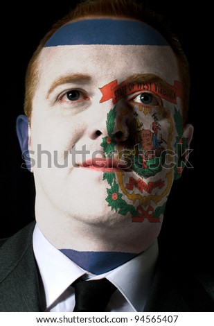 High key portrait of a serious businessman or politician whose face is painted in american state of west virginia flag - stock photo