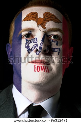 High key portrait of a serious businessman or politician whose face is painted in american state of iowa flag - stock photo
