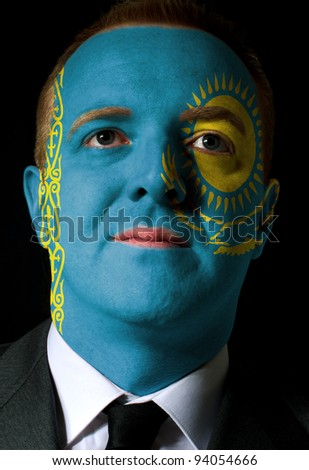 High key portrait of a serious businessman or politician whose face is painted in national colors of kazakhstan flag