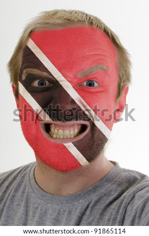 High key portrait of an angry man whose face is painted in colors of trinidad and tobago flag