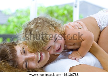 High key portrait of happy mother with baby