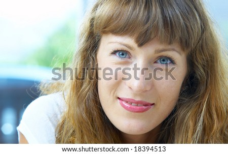 high-key portrait of young blue eyed woman on color back