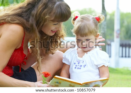High key portrait  of young mother reading a book for her baby