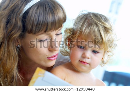 High key portrait  of young mother reading a book for her baby . focused on baby's face - stock photo
