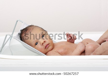 High key shot of a baby in a bath. - stock photo