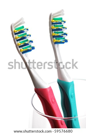 High key shot of two toothbrushes in a glass against white background - stock photo