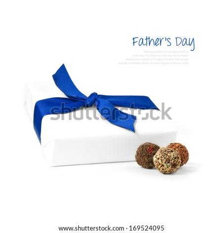 High-key simple white gift tied with a blue ribbon with chocolate truffles against a white background. Copy space. - stock photo