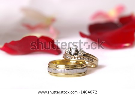 high-key wedding bands on pure white background with rose petals - stock photo