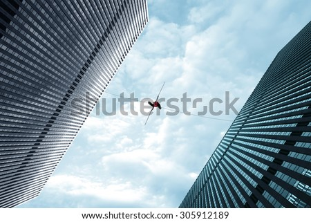 High-line walker in blue sky between two buildings concept of risk taking and challenge - stock photo