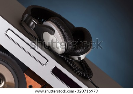 high loudspeaker tower with cd player headphone over black background