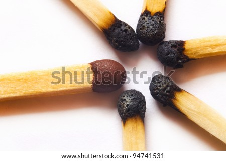 High magnification macro photo of single match standing out against group of used, burned matches. - stock photo