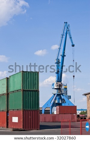High mobile crane surrounded with containers - stock photo