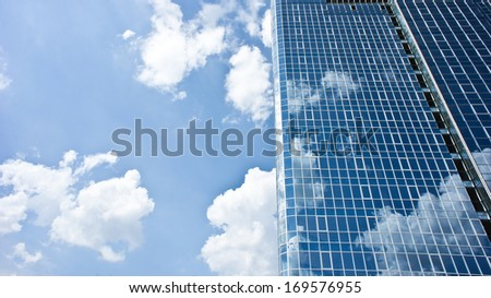 High modern skyscraper on a background of the blue sky and clouds on it with reflection on the building - stock photo