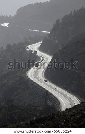 High mountain foggy view of a serpentine type jammed road.Backlite picture. - stock photo
