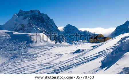 high mountain hut, mountains peaks and traces of the skis