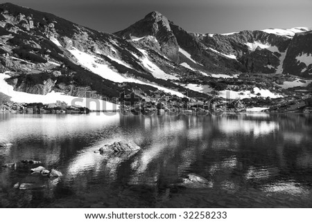 high mountain reflection of the water on black and white - stock photo