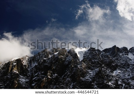 High mountain ridge and snow rocks under the blue sky and white clouds and mist. Aktru, Altai, Siberia, Russia.