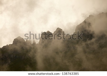 High mountain ridge in thick fog - stock photo
