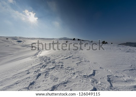 High mountain sunny view with isolated trekker on trail