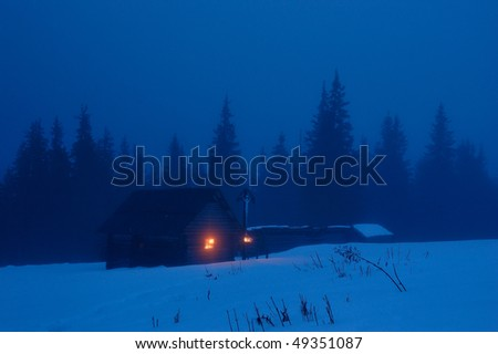 High-mountainous small house in the Ukrainian Carpathians. Winter evening, on a cross with Jesus burns a candle - stock photo